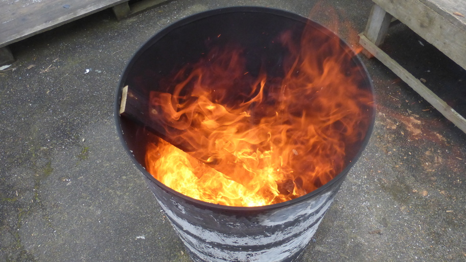 In einer grauen Tonne lodert wärmendes Feuer.