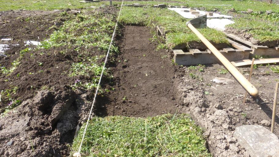Für Rasenstücke vorbereitetes Wiesenteilstück, rechts liegen Rasenstücke auf Paletten geparkt.